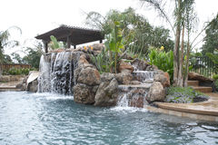 A pool with a waterfall in a luxury backyard stock images