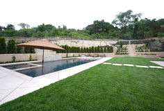 A pool with a waterfall in a luxury backyard Royalty Free Stock Photography