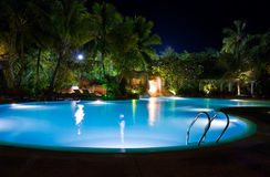 Pool and waterfall at night. Vacation background Stock Photography