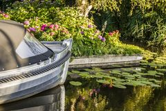 The bow of a pleasure yacht in a pond with water lilies. A pool with waterlilies and the bow of a pleasure yacht in the shining water on a sunny day Stock Images