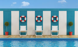 Pool with white deckchairs Stock Photos
