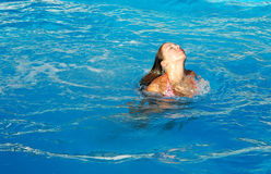 The pool1. Young woman coming up after diving into pool Stock Photo