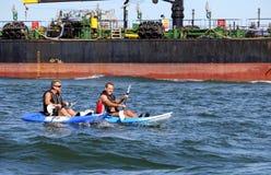 Poole Dorset, England - Juni 02 2018: Åldrades caucasian mitt två män som kayaking på det öppna havet i vaken av en enorm oljetan royaltyfri fotografi