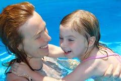 Poolmutter und -tochter, die zusammen schwimmen spielen Stockbilder