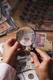 Pools zloty en vergrootglas in de vrouwen` s hand Royalty-vrije Stock Afbeeldingen