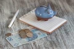 Pools zloty, notitieboekje en spaarvarken op de houten achtergrond Stock Afbeelding