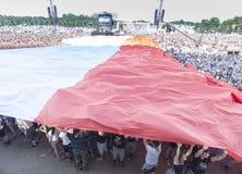 Poolse die vlag met publiek wordt uitgespreid Stock Fotografie