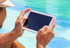 Poolside ταμπλετών εκμετάλλευσης ατόμων Στοκ εικόνες με δικαίωμα ελεύθερης χρήσης