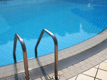 Poolside. Side of a filled pool and handle Stock Photos