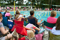 το πλήθος συναντά το poolside προγόνων κάθεται κολυμπά στο ρολόι Στοκ Φωτογραφίες