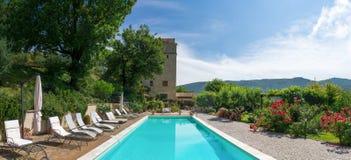 Poolside allo stagno classico del palazzo e giardino che esamina torre Immagini Stock Libere da Diritti