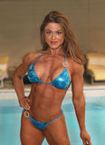 Poolside Beauty. Gorgeous, alluring Canadian IFBB Pro Figure and Physique competitor and fitness model, Debbie Barrable poses with a teal bikini displaying her Royalty Free Stock Photos