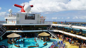 Poolside on the Carnival Breeze. The Breeze is a Dream-class cruise ship owned by Carnival Cruise which entered service in June 2012 Royalty Free Stock Photo