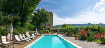 Poolside at classic mansion pool and garden looking at tower. The pool area at a mansion in italy sunny day Royalty Free Stock Images