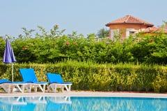 Poolside con las cubierta-sillas y el paraguas doblado Fotografía de archivo libre de regalías