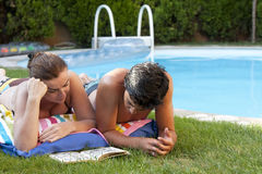 Poolside couple. A couple is restin near the backyard pool as both read a book on the grass Royalty Free Stock Photo