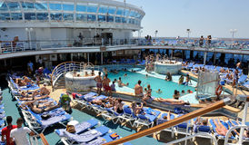 Poolside cruise ship. Lots of people relaxing at the deck chairs of cruise ship the Crown Princess Stock Image