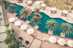Poolside d'hôtel avec des parasols et des paumes Image libre de droits