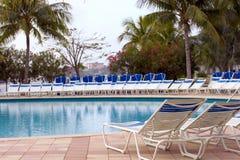 Poolside de las sillas de cubierta - primero plano del foco Fotografía de archivo libre de regalías