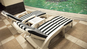 Poolside deck chairs Stock Photo