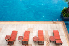 Poolside deckchairs alongside blue swimming pool Royalty Free Stock Photography
