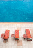 Poolside deckchairs alongside blue swimming pool Royalty Free Stock Photos