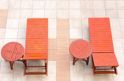 Poolside deckchairs alongside blue swimming pool from top view Royalty Free Stock Images