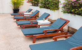 Poolside deckchairs with blue swimming pool royalty free stock images