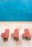 Poolside deckchairs neben blauem Swimmingpool Lizenzfreie Stockfotos