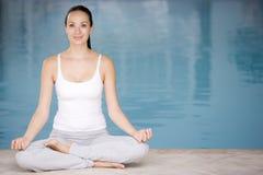 Poolside di seduta della donna che fa yoga fotografia stock libera da diritti