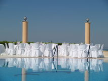 Poolside event setup. A picture of chairs and covers, set up next to a pool, for a poolside wedding stock image