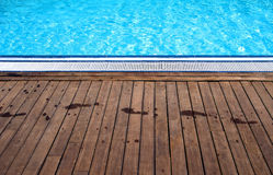 Poolside with footprints. Swimming pool showing the wooden poolside with wet footprints royalty free stock images