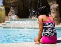 Poolside hermoso de la muchacha que se relaja por una cascada Imagen de archivo libre de regalías