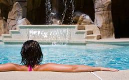 Poolside hermoso de la muchacha que se relaja por una cascada Fotografía de archivo