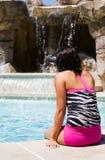 Poolside hermoso de la muchacha que se relaja por una cascada Imágenes de archivo libres de regalías