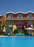 Poolside Holiday Hotel. Holiday apartments of a hotel in Turkey with pool and flowers in teh foreground Stock Photo