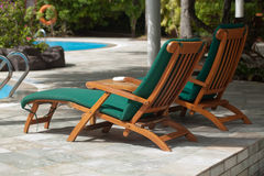 Poolside lounge chairs. Two poolside lounge chairs along the swimming pool Royalty Free Stock Photo