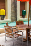 Poolside loungers at hotel. Swimming pool surrounded by chairs Royalty Free Stock Photography