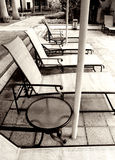 Poolside loungers, monochrome. A row of poolside lounge chairs, outdoor furniture made with rattan cane and wrought iron frames, placed by the side of the Royalty Free Stock Image
