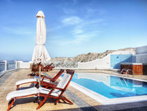 Poolside. Luxurious patio water pool and sun loungers Stock Photos