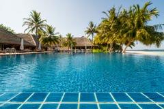 Poolside mit tropischem Erholungsort als undeutlichem Hintergrund stockfoto