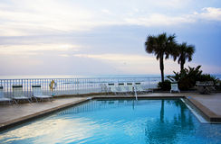 Poolside at an ocean sunrise. Poolside of a hotel at the Atlantic Ocean Stock Image
