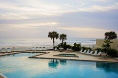 Poolside at an ocean sunrise. Poolside of a hotel at the Atlantic Ocean Stock Photography