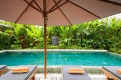 Poolside och stor slags solskydd Fotografering för Bildbyråer
