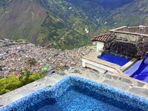 POOLSIDE OVERLOOKING TOWN IN THE VALLEY, BANOS ECUADOR. Have a swim while looking down into the valley of the Andes from the pool at Luna RunTun. You will have a Stock Photography