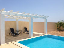 Poolside pergola, gazebo providing shade. White poolside pergola, gazebo providing shade on a terrace patio area next to a swimming pool. Mobilestock stock photography