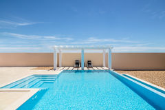 Poolside pergola and infinity swimming pool royalty free stock images