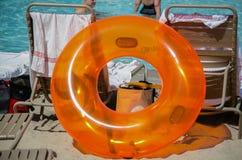Poolside plástico anaranjado grande del tubo interno con las sillas de cubierta en Sun Fotos de archivo