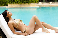 Poolside prendente il sole della giovane donna in un bikini Fotografia Stock Libera da Diritti