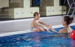 Poolside se reposant de petit fils contagieux de jeune femme dans la piscine Photographie stock libre de droits